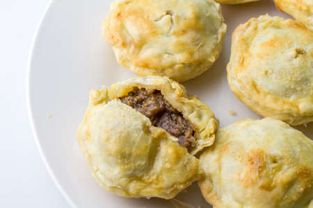 Steak pies on a plate - mini beef pies on white background with copy space