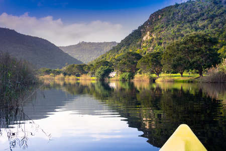 Scenic river canoe trip with tranquil reflections of mountains and trees on river edge near Knysna in South Africa Banque d'images