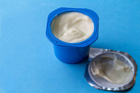 Yogurt cup with creamy yoghurt in blue pot and foil lid isolated on blue background with space for text Banque d'images