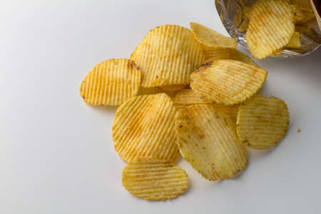 Heap of potato crinkle chips isolated on white background with text space
