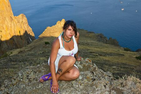 Girl sits on the edge of a cliff over the sea