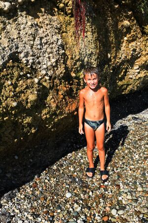 aqua naked: A little boy in a bathing suit is a coastal cliff