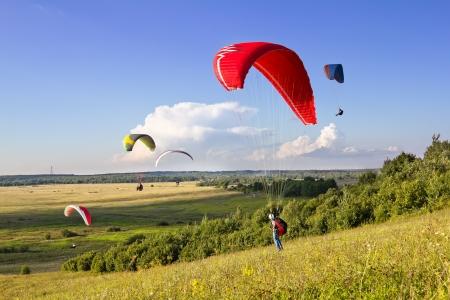 parapente: Meerdere paragliders zweven in de lucht te midden van wonderlijke landschap