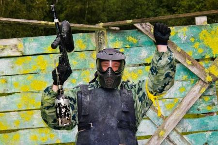 Paintball giocatore alzò la mano con una pistola sullo sfondo di un rifugio in vernice Archivio Fotografico - 15037769