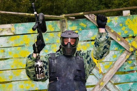 Paintball player raised his hand with a gun against the backdrop of a shelter in paint
