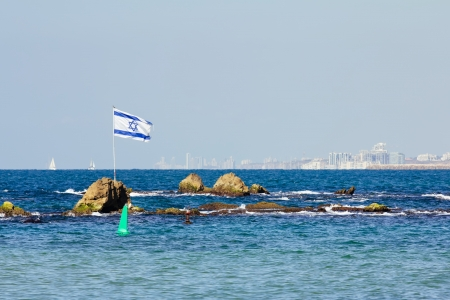 The Israeli flag flies at the entrance to the port of Jaffa photo