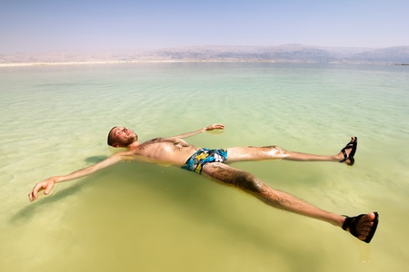 A man rests his hand on the water of the dead sea in Israel photo