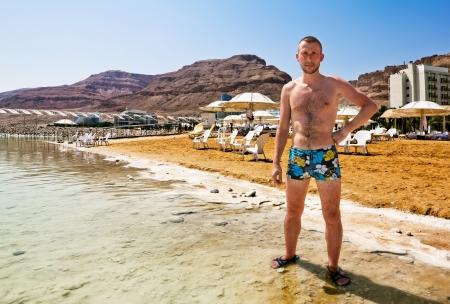 Ein Mann in Badehose steht am Ufer des Toten Meeres in Israel vor dem Hintergrund der Berge Ein Mann in Badehose steht am Ufer des Toten Meeres in Israel vor dem Hintergrund der Berge