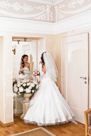 Bride in wedding dress looks in the mirror