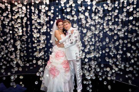 Newlyweds in wedding attire posing in scenery of glass balls Stock Photo - 17575973