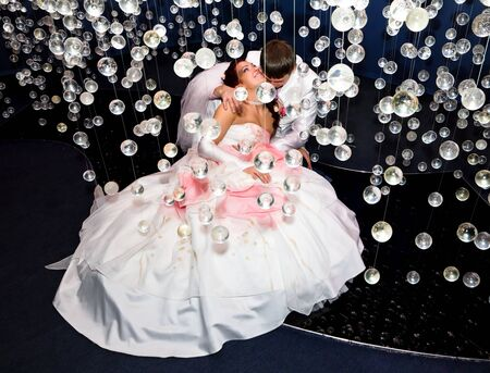 Newlyweds in wedding attire posing in scenery of glass balls