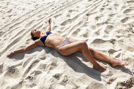 Girl in a bikini lying on the sand at the beach with open hands