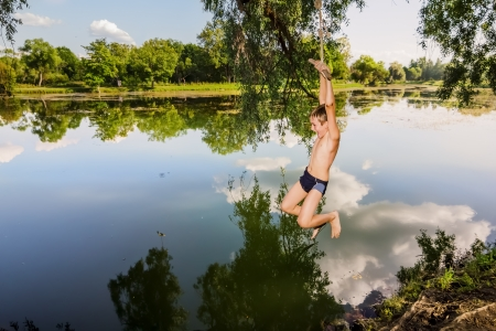 A boy jumps in a lake with a rope from a tree Stock Photo
