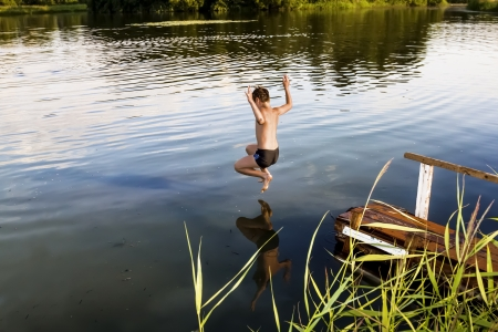 A boy jumps in a lake with a take-off on a summer day