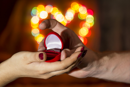 A man gives a woman a ring against the backdrop of a colorful heart-shaped bokeh photo