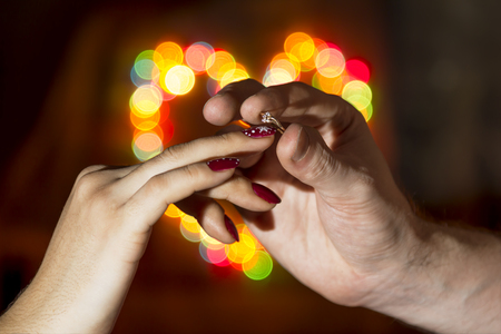 The man wears a woman s finger ring against the backdrop of a colorful heart-shaped bokeh photo