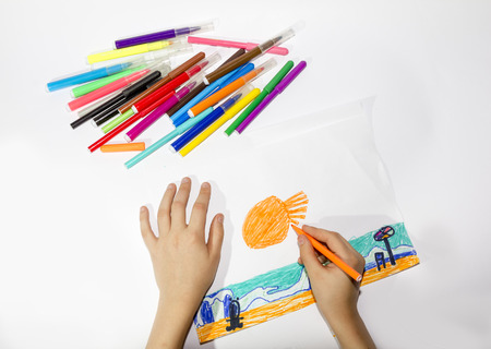 The boy draws a picture set of multicolored markers