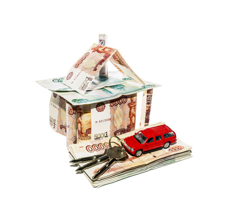 House made of banknotes with a toy car and a bunch of keys on a white  photo
