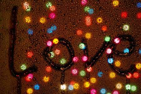 The word  love  is drawn on a wet glass on the background of colorful circle Bokeh