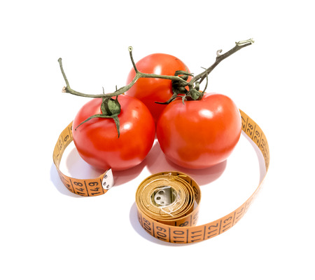 Tomatoes on a branch in a centimeter tape on white background photo