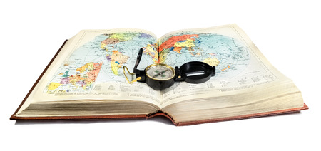 Compass lies on the terrain map, atlas book on white background Stock Photo