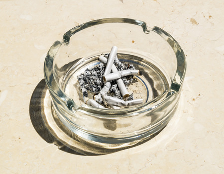 Cigarette butts from ash in the glass ashtray on a stone table top photo