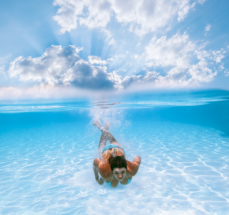Girl swims under water in the pool against the backdrop of the beautiful heavenly scenery photo