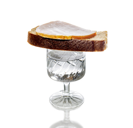 A glass of vodka with a sandwich there, isolated on white background photo