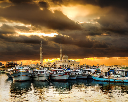 ported: Yachts berthed at the port of Hurghada at sunset against the mosque