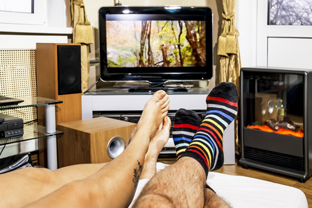 looking at watch: Womens and mens feet in socks in the living room watching TV Stock Photo