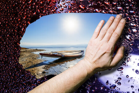 Hand wipes the wet glass and, through him, to the visible solar seascape