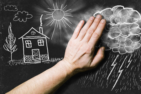 Drawing with chalk on the Blackboard: the hand wipes the clouds over the landscape with the House