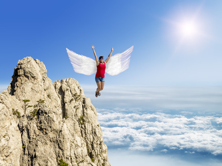 inair: Girl flies on the wings against the background of clouds and mountain peaks, fantastic image