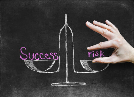 unbalanced: The success and risk at different scales-drawing with chalk on the Blackboard.abstract illustration Stock Photo