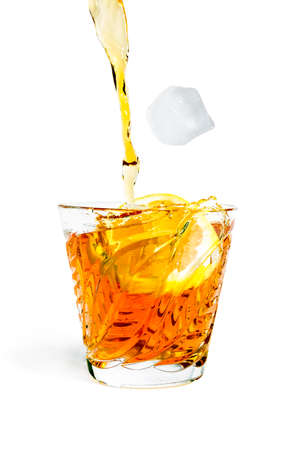 whiff: Ice cube falls with splashes into the glass with alcohol isolated on white background