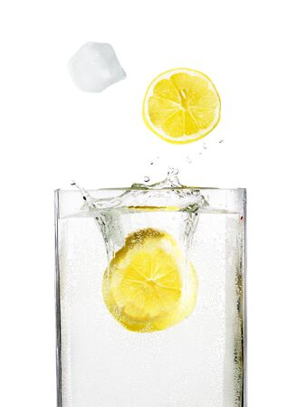 lobule: Ice cube with lemon drops from splashes into the glass with alcohol isolated on white background