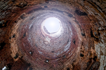 tunel: View from inside the old brick industrial pipes with a bright light at the end of the pipe