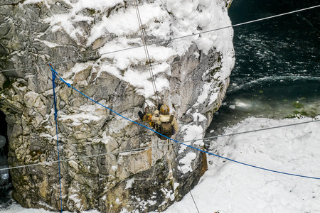 abseil: Male in mountain climbing gear is coming down to a cave in the Mountain Park of Ruskeala in Karelia, Russia , 01 March 2015