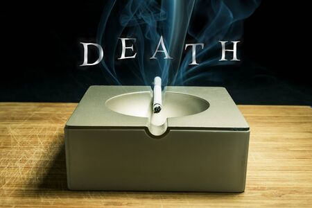 smoldering: Smoldering cigarette in the ashtray with the inscription of smoke death close-up