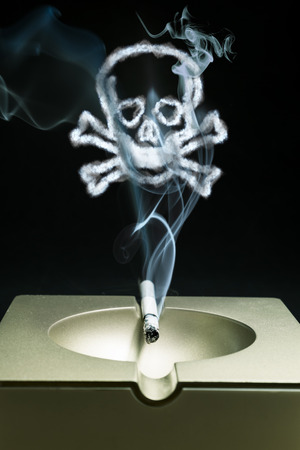 smoldering: Smoldering cigarette in an ashtray with a smoke skull close-up