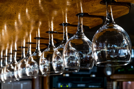 bar ware: Wine glasses hang on the wooden bar stock