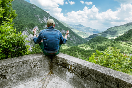 tara: man in a lotus position meditating above the canyon of the river Tara Stock Photo