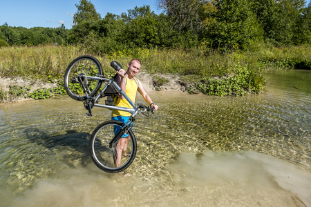 carrying the cross: Cyclist holding his bicycle, standing in a river in sunny day