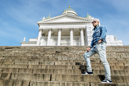 senate: man poses on the granite stairs at the Cathedral on the Senate square in Helsinki Finland Stock Photo