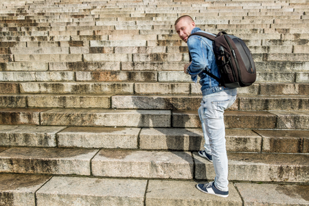 concrete stairs: Male tourist with backpack climbs up the granite stairs