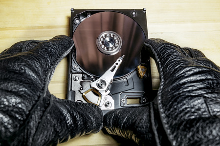formatting: the hard drive from the computer in the hands in gloves on a wooden surface Stock Photo