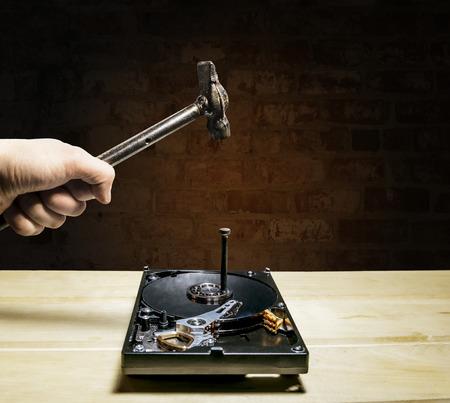 hard drive crash: A hammer hits a nail into the hard drive from the computer against a brick wall