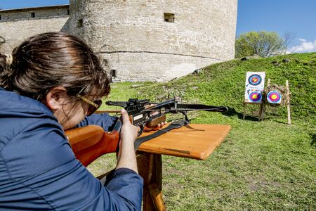 crossbow: 02 may 2016. Staraya Ladoga.Girl shoots a crossbow from the walls of the fortress in Staraya Ladoga.Russia.
