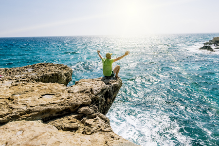 25 may 2016.Cape Greco.A man sits on a ledge of rock above the sea at Cape Greco . Cyprus. Stock Photo