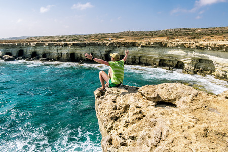 ledge: 25 may 2016.Cape Greco.A man sits on a ledge of rock above the sea at Cape Greco . Cyprus. Stock Photo